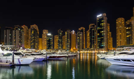 DUBAI, UNITED ARAB EMIRATES - 05 DECEMBER, 2018: Panoramic view with modern skyscrapers and water pier of Dubai Marina, an artificial canal city in Dubai, United Arab Emirates