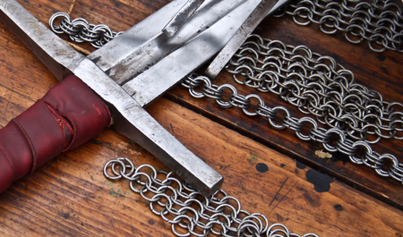medieval sword: Sword laying on a table, a circuit and a chain armour.