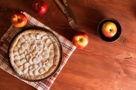 Delicious and warm homemade apple pie on a wooden table. Around him are apples, and cutlery. Pie on pottery. Photographed from above. Stock Photo