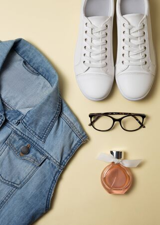 Denim vest, white sneakers, glasses and perfume. Top view Stok Fotoğraf