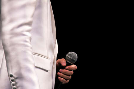 a singer holding a microphone Stock Photo