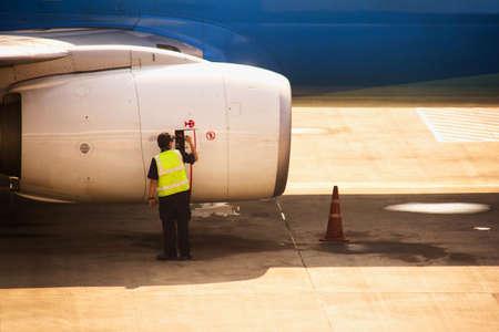 Aircraft mechanic checking ariplane jet engine 報道画像