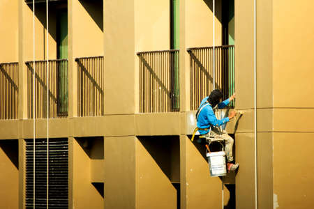 a painter painting on high rise building