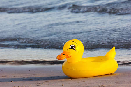 duck rubber ring, duck swim-ring on the beach photo