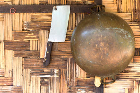 brass pan and chopping knife hanging on the woven bamboo wall of house photo