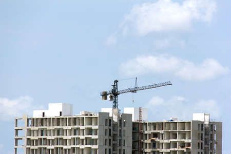 dwelling mound: Construction site with cranes against blue sky