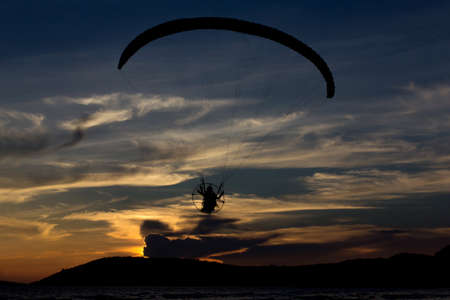 Silhouette paramotor  flying  on the sky with sea view photo