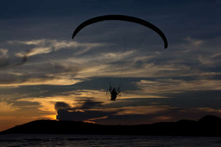 Silhouette paramotor  paraglider flying  on the sky with seaview photo