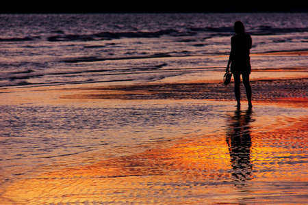 disconsolate: young woman silhouette on the beach in sunset background Stock Photo