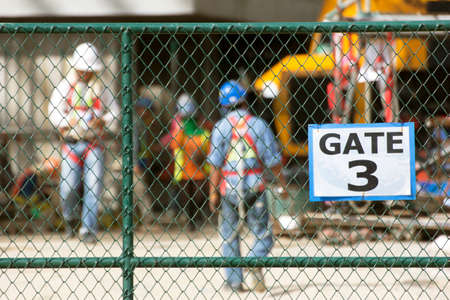Workers in construction site, focus on chain link fence. Stock Photo
