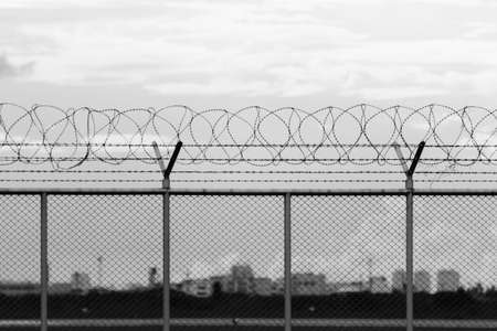 lockup: security restricted area with a barbed wire fence, black and white photo