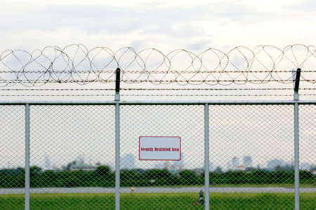 barbed wire fence: security restricted area with a barbed wire fence Stock Photo