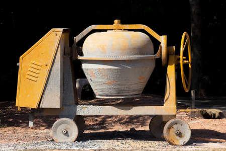 taskmaster: Industrial cement mixer machine at construction site.