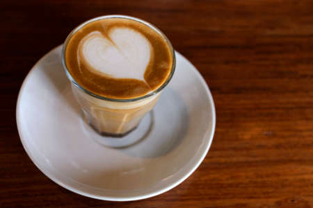 heart drawing on latte art coffee on wood table background