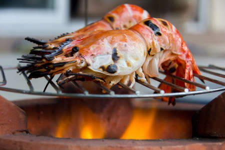 macrobrachium: grilling giant freshwater prawn on a charcoal brazier with selected focus