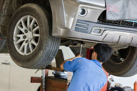 scheduled replacement: Bangkok, Thailand - January 21 : automobile mechanic examining car suspension of lifted  automobile at at MItsubishi Motor Service station on January 21, 2015. Bangkok, Thailand. Editorial