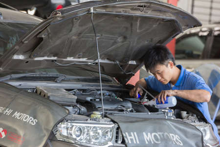 scheduled replacement: Bangkok, Thailand - January 21 : automobile mechanic examining car suspension of lifted  automobile at at Mitsubishi Motor Service station on January 21, 2015. Bangkok, Thailand.
