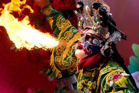 Chinesisches Neujahr, Chinesische Oper Schauspieler spucken Feuer in der traditionellen ausführen Gesicht verändernden