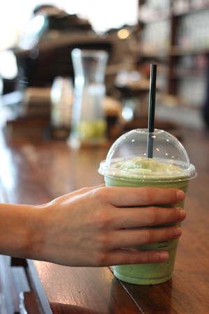 custumer: custumer picking up blended green tea frappe in coffee shop Stock Photo