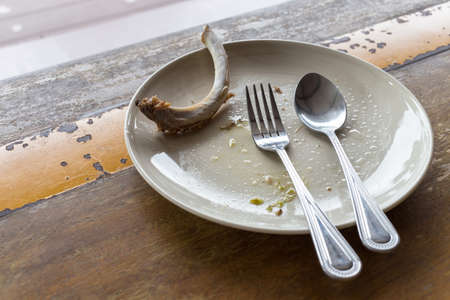 after the party: finished meal after party, rib bone in empty plate with spoon and fork on wood table