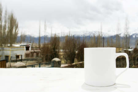white coffee cup with Himalaya mountain view at Ladakh, India