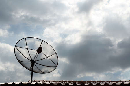 Satellite dish communication technology network on the roof in the cloudy day