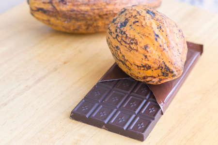 fresh cocoa pod and chocolate bar on the wooden background
