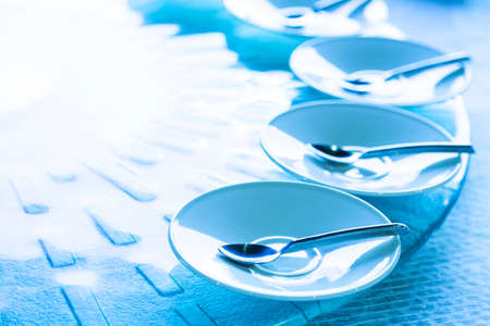 spoon in the white dish on the food table, selective focus and blue tone