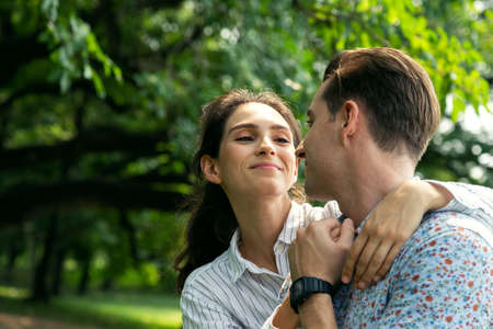portrait smiling young man and woman couple in love hugging in the park at summer season with warm sunlight. people and lifestyle concept.