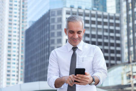 stock trader, investor, businessman happy after checking profit on investment portfolio from stock market on smartphone application at business office building center. business and financial concepts. Stock Photo