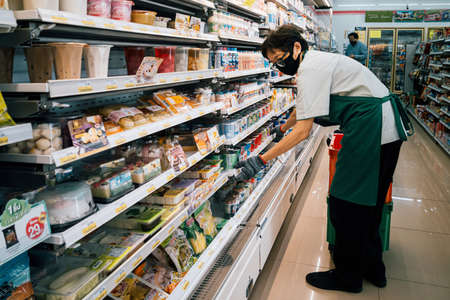Bangkok, Thailand - August 3, 2020 : asian woman shop assistant wearing hygiene face mask are restocking product to shelf in supermarket at coronavirus pandemic or covid-1 outbreak.