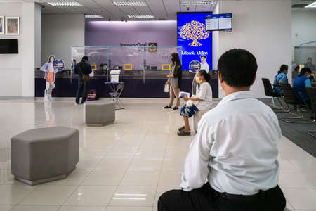 Bangkok, Thailand - August 4, 2020 :  people wearing face mask to protect from coronavirus pandemic or covid-19 virus outbreak keep distance  to do transaction and personal finance in bank office.