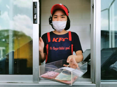 Bangkok, Thailand - August 3, 2020 : KFC fast food cashier in drive thru service waring hygiene face mask to protect coronavirus pandemic or covid-19 virus outbreak is giving money change to customer.