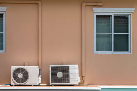 two types of home air conditioner compressor coil installation at the balcony under the window of the house.