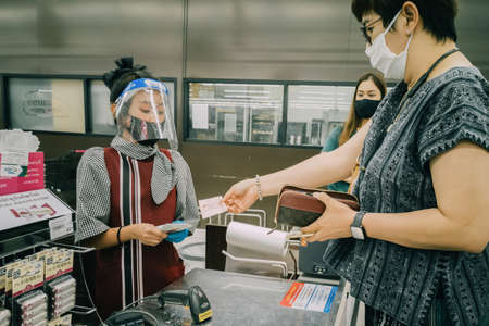 Bangkok, Thailand - October 1, 2020 :  asian woman shoppers and cashier wearing hygiene face mask to protect from coronavirus pandemic or covid-19 virus outbreak in supermarket . social distancing.