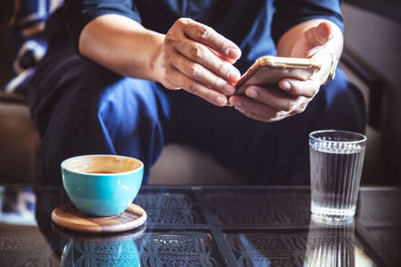 businessman using smartphone to read investment news and reply email to confirm meeting in coffee shop. man drinking latte coffee before going to work on monday morning. vintage photo and film style