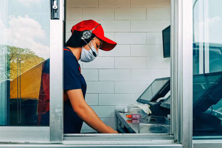 Bangkok, Thailand - August 4, 2020 : fast food cashier in drive thru service waring hygiene face mask to protect coronavirus pandemic or covid-19 virus outbreak working on counter at the station.