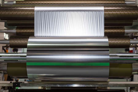 roll of aluminum foil for food packaging on the automatic packing machine in food product factory. industrial and technology concept. Reklamní fotografie