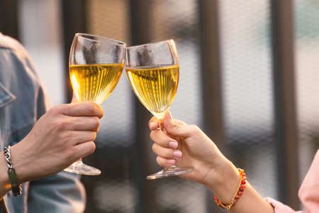 close up hands of lovers couple man and woman cheering and toast with white wine glasses to celebrating at a dinner party in the summer time. love, celebration, relationship and romantic concept. Stock Photo