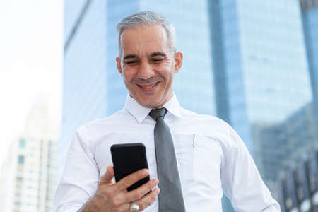 stock trader, investor, businessman happy after checking profit on investment portfolio from stock market on smartphone application at business office building center. business and financial concepts. Reklamní fotografie