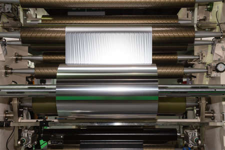 roll of aluminum foil for food packaging on the automatic packing machine in food product factory. industrial and technology concept. 写真素材