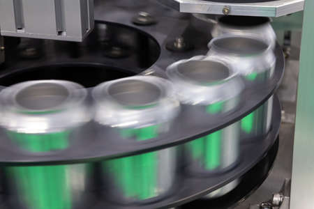 empty new aluminum cans for drink process are moving in factory line on conveyor belt machine at beverage manufacturing. food and beverage industrial business concept.