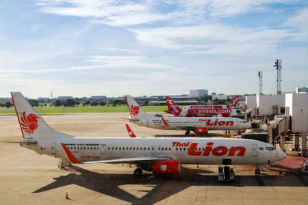 Bangkok, Thailand - August 3, 2020 : Lion Air and  AirAsia airplanes in parking bay at airport terminal after flight cancellation during coronavirus pandemic or covid-19 virus outbreak. Editorial