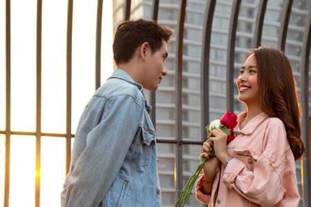 young happy couple love and romantic at first date relationship. asian teenage woman surprise and smiling at boyfriend gives red rose flowers at dinner in valentine day. couple and happiness concept. selective focus. Reklamní fotografie
