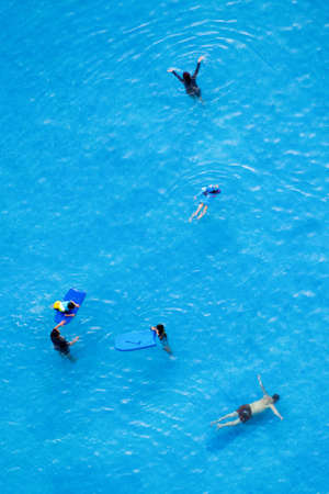 top view of man, woman and children are relaxing and enjoy activities in the swimming pool of the luxury hotel and resort at summertime. summer holiday vacation idyllic. travel and hotel concept 写真素材
