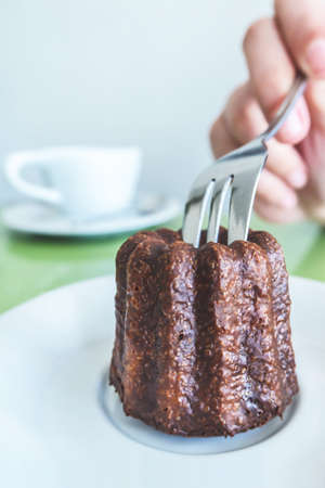 traveler woman hand holding a fork and cutting a Canelé (Canele - Caneles de bordeaux) traditional French sweet dessert bakery with white coffee cup background in coffee shop in Paris. food and lifestyle concept.