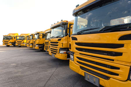 new yellow trailer truck car fleet with container depot on truck manufacturing factory parking to deliver to business shipping and logistic company client. transportation and logistic industry concept Reklamní fotografie