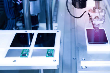 automatic robot arm with vacuum sucker working in the production line and assembling smartphone screens in the new innovative and high technology smartphone factory. Stock Photo