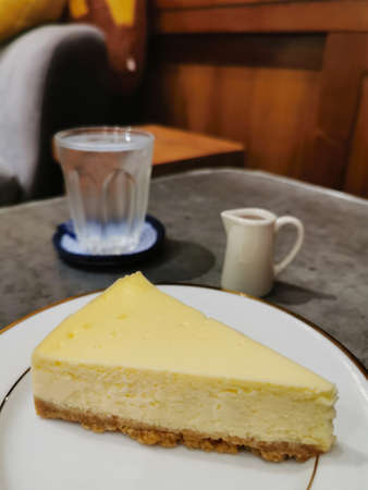 slice of plain traditional new york cheesecake on the white plate ready to serve in the bakery shop. Reklamní fotografie