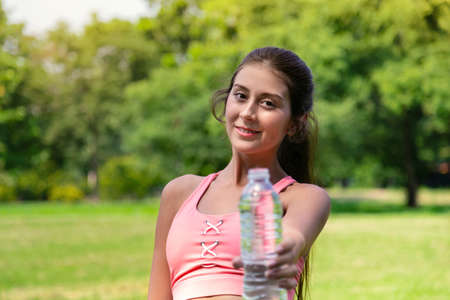 smiling young teenage girl in sport suit drinking and give water bottle to friend for good healthy life after running exercise in park with warm sunlight on summer morning. people and healthy lifestyle concept. Reklamní fotografie